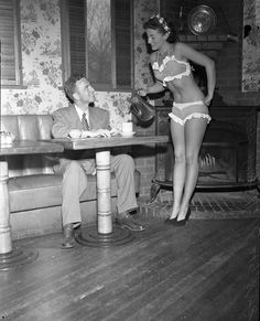 """Pat Hall, """"Miss 7-Cent Cup of Coffee, 1950,"""" serving William E. Kinman coffee while wearing a bikini, Los Angeles, CA  c.1950."""