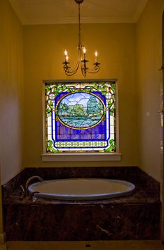 Stained glass is a unique way to add privacy and beauty to bathroom windows. Check out our website for information on ordering a similar custom element for your own home. Design by Stanton Studios.