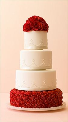 red-rose-bedecked white wedding cake.