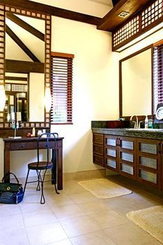 In line with the Modern Filipino design of the house, the bathroom is decorated with capiz window panels. The capiz panels serve as lighting fixtures above the his-and-hers sinks and as a frame for the dresser mirror. The vanity area is completed with the same metal chair designed by architect Jouie. The high ceiling of the space makes the area look bigger than it really is.