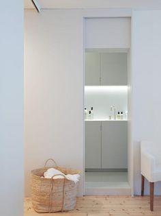 MINIMALISTISK: Vaskerommet du ser gløtt av her er mer påkostet enn man skulle tro ved første øyekast. Her er nemlig både vegger og gulv, skapfronter og vask laget i komposittmaterialet Corian. Prosjektet er ved arkitekt Henrik Nømm, a-tract.no.