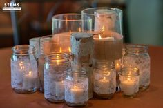 Some of the centerpieces will be clusters of pillar candles in vases wrapped in burlap, birch logs and mason jar candles wrapped in lace at varied heights.