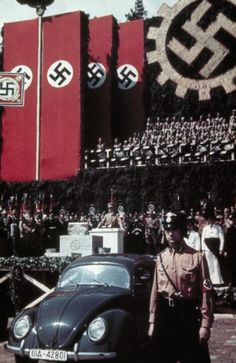 June 1938: Adolf Hitler makes a speech during a cornerstone-laying ceremony to mark the start of construction of the Volkswagen factory at Fallersleben. In the foreground is the prototype Volkswagen car designed by Prof Dr F Porsche and handmade by the Mercedes Benz car factory.
