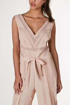 Chic V-neck jumpsuit with intricate crochet detailing and wrap front detail. Wide leg fit and hidden side zip closure.