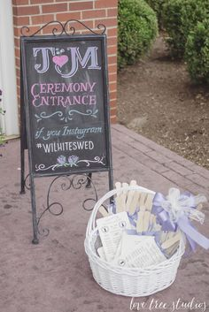 Wedding chalkboard at the entrance and program fans displayed in a wicker basket for guests. Have guests add a hashtag to photos they snap during the day so you and your new spouse can look through all of them later!   AnnaBelle Events