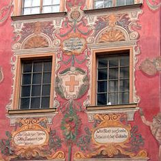 The painted façade of a café in Chur, capital of Canton Graubünden. The upper inscription commends the building to God, and says it is named the Golden Cross. The lower inscriptions say the decoration is to beautify the city, to honour craftsmen, and to bring joy to art.