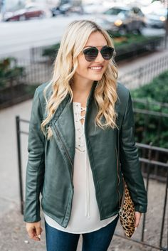 Bows & Sequins wearing a green leather jacket, a lace-up blouse, and Dior sunglasses.