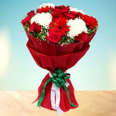 A lovely bouquets of 15 red roses , 6 Red Gerberas , 5 White Chrysanthemum decorated with red paper packing and featured with green & white ribbon together makes a perfect gift to impress at a single glance In Gurgaonflorist.com