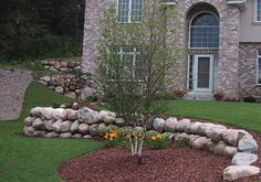 A smaller boulder wall creates two nearly level areas in the front yard instead of one large expanse of grass. Note how the color in the boulders complements the color of the brick on the house.