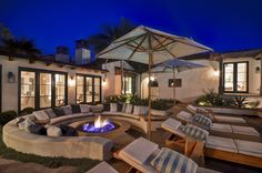 A perfect way to end an evening with a cozy backyard fireplace and wrap around sofa.   Very resort like and incredible for gathering patio ideas for you own DIY home projects.  A design style and decor choice that can fit most homes. A dream home inspired backyard patio.