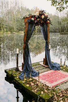 Our rustic arch, vintage rug and candlesticks by the lake for a wedding ceremony