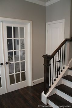 Love this color combo!....dark wood flooring and railing with white and an off gray!