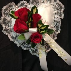 """Casket pillow flowers - funeral arrangement – sympathy flowers: This is a casket pillow ordered by grandchildren for their grandfather's funeral flowers. This casket pillow is a white heart-shaped pillow edged with lace complimented with red roses and """"Loving Grandpa"""" in gold lettering on the bow."""