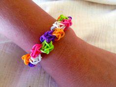 Pulsera de arco iris telar de gomas en color de rosa, naranja, púrpura, verde neón y brillando intensamente en las bandas oscuras. estirable.