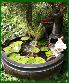 A fountain and small water garden made from an old whiskey barrel and an old water pump
