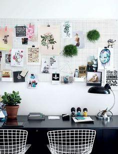 Decoração de apartamento pequeno, mini apartamento, home office, escritório em casa, com pegboard, paredes brancas, mesa preta e cadeira branca.