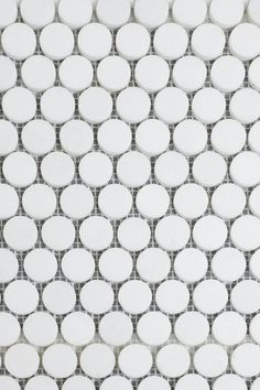 """Bright white marble from Greece with dramatic unstructured soft to deep blue/grey veining in the traditional 1"""" penny rounds shape. White Thassos marble penny round tile backsplash 