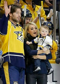 Carrie Underwood and Mike Fisher with their 1 yr. old son, Isaiah celebrating Mike's 1000th game