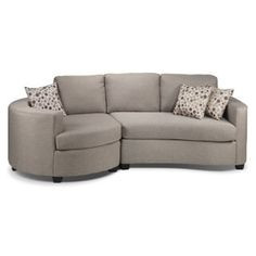 """Andrea 2 Pc. Sectional - Gentle Curves. The curved lines of the Andrea sectional sofa welcome you to sit down, relax and curl up for a while. A heathered graphite finish and soft contours present a casually modern look. Small wedge feet supply a little lift while the toss pillows' accent fabric with small, multihued circles and wavy, white lines provide a contemporary """"pop"""" in your living room. Two-piece sectional includes left-facing bumper loveseat and right-facing curved loveseat, as…"""