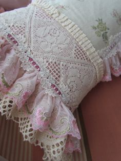 I covered the main green checkered material of the cushion completely..  First I put linen with the letters and stitched pink lace and a velvet ribbon through  lace on top of that.  Behind the big crochet lace I put pink satin ribbon and gathered   cotton lace on one side and two layers of lace on the outside.. and finished it of   with ribbon through lace.