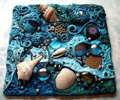 This is a mosaic tile I made with polymer clay on hardboard. I included sea shells, glass gems, crystals, textured metal disks and a really awesome polymer clay cabochon that I traded with another artist for. I can't remember who it was for the life