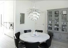 """Clean white kitchen, Poul Kjærholm PK54 in marble (dream table!), artichoke lamp and Arne Jacobsen """"syver"""" chairs in black leather. The streamlined look is mixed with an old vitrine cabinet in grey where the Royal Copenhagen's mussel blue fluted plain is exhibited"""