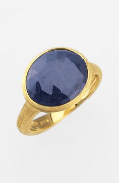 'Siviglia' Faceted Sapphire Ring The natural Beauty of an Untreated Sapphire shines within an Oval Bezel setting in a demure, hand-engraved Ring forged from 18-karat Yellow Gold. Blue or Red-Pink Raw Sapphire By Marco Bicego; Made in Italy.
