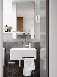 espelho com borda oval e torneira branca em banheiro