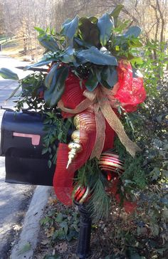 Christmas Mailbox Decoration - Bright Red Deco Mesh with Gold Woven Ribbon wrap up Evergreens and Magnolia - set off by Oversized Bright Red and Gold Ornaments.