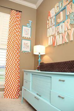 Cute idea for a nursery -- alphabet wall with the first letter of their name framed. Love the colors.