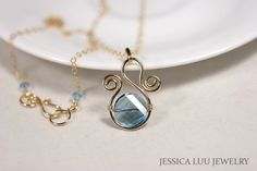 Gold wire wrapped necklace handmade by Jessica Luu Jewelry on Etsy Aquamarine necklace is made with: ~ 14mm aquamarine Swarovski crystal twist bead ~ Hand formed 14K gold filled wire frame ~ 14 karat gold filled chain ~ 14 karat gold filled hook and eye clasp with 4mm aquamarine crystal accents Dimensions: ~ 18 inches long ~ Pendant hangs 1.5 inches from chain and is nearly 1 inch wide Earrings: ~ 8mm aquamarine Swarovski crystals ~ 14k gold filled wire ~ Ear nut backings ~ Just over inch…