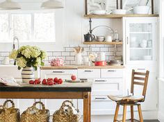 Love this rustic/renovated kitchen from Country Living! Inexpensive updates--white paint, big-box cabinetry, subway tile, butcher-block counter tops--lightened up this once gloomy kitchen. An antique bakery table-turned-island offers extra prep space and storage.