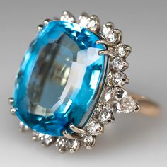 This lovely vintage blue topaz cocktail ring features a centered 38.88 carat rectangular cushion blue topaz . The gemstone is sitting atop an openwork wire gallery and is four prong set. The topaz has a lovely diamond halo. The shoulders of the ring each feature a pear cut diamond accent and one of the pear accent diamonds has a small ship.  This ring is crafted of solid 14k two-tone gold and is in good overall condition but the topaz does show some wear and abrasions.  There is currently a…