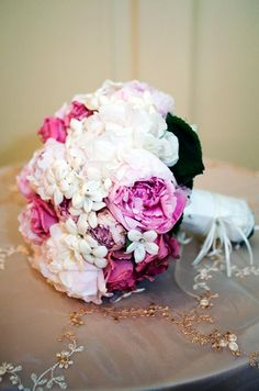How pretty is this wedding bouquet of peonies and embellished stephanotis wrapped in white silk?