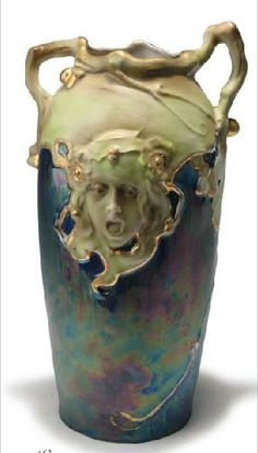 Carl Knoll, Karlsbad. Earthenware. Art Nouveau vase with girl's head; c. 1920, twisted, irregular branch forms handles; iridescent purple, blue green glaze, gold highlights, H. 31.5 cm, base marked