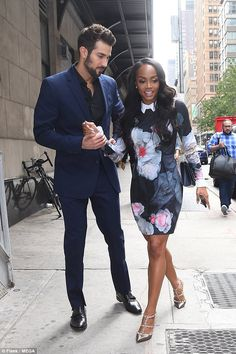 Chic couple: Bryan looked dapper in a blue suit and black shirt while his petite fiancee looked fab in a flower minidress and sparkly silver Valentino high heels