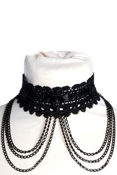 This gothic choker by Sinister is made from a pretty black lace brocade threaded with black satin ribbon and detailed with black satin roses, black chains and a black skull at the centre front.