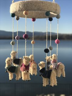 I want this cute mobile for kids room! This baby mobile is made from llama ornaments with added knitted sweaters and felted pom poms.