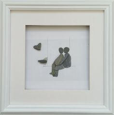 Ideal Valentines Day/Anniversary gift.  A pebble couple on a swing along with a bird and a granite heart set inside a 25cm x 35cm glazed box frame in either black or white.  Words can be added to the mount at no extra cost.  A small sea glass heart can be added in place of the granite one.