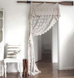 crocheted table cloth with boat oar rod... would really like it as a window treatment.