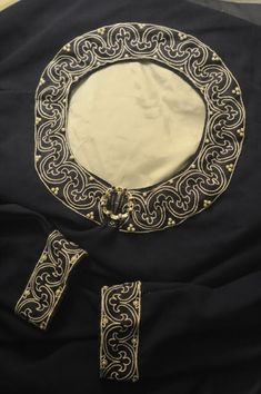 """The embroidery is done in split stitch with two strands of white silk embroidery floss on dark blue linen and ~4mm button pearls sewn with silk thread. The pattern is from a 12th century German altar frontal--the cuffs have it as-is, the collar is adapted for the shape."""