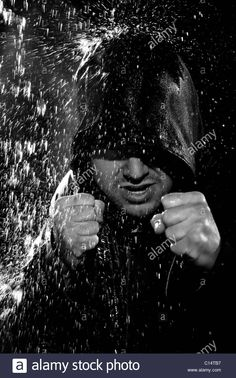 A young man wearing a hooded jacket poses in a wushu stance while it rains down on him. Stock Photo