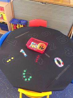 Black paper stuck onto table, draw around numbers and leave out counters - simples!