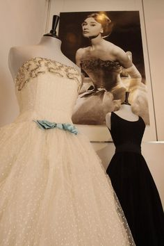 Audrey Hepburn's Givenchy white point d'esprit ball gown from the 1956 film 'Love in the Afternoon' is displayed with a black Elizabeth Arden goffered cocktail dress from 1953.