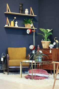 In our store; dark blue wall + yellow ocher fifties chair + swedish design vintage commode + messing table + shelves hanging on the wall with leather straps + bordeaux sixties lamp + plants. How we like our interior!
