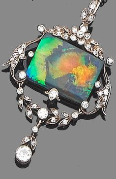 A belle époque black opal and diamond pendant necklace, circa 1905 The openwork cartouche, set to the centre with a rectangular cabochon black opal, within a millegrain-set single-cut diamond surround, suspended from a trace-link chain, diamonds approx. 0.70ct. total, lengths: pendant 4.9cm., chain 38.4cm.