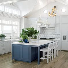 The oversize island and industrial-style pendants suit this kitchen's grand scale. | Coastalliving.com