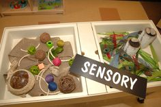 Students engage their senses at the sensory table in the toddler classroom.
