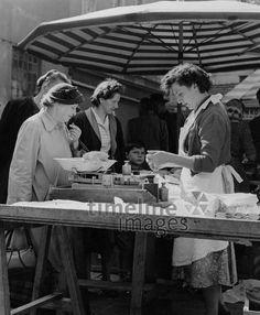 Marktfrau wiegt Hendl auf dem Münchner Viktualienmarkt, 50er Jahre Stöhr/Timeline Images #black #white #schwarz #weiß #Fotografie #photography #historisch #historical #traditional #traditionell #retro #vintage #nostalgic #Nostalgie #München #Munich #50er #1950er #Stimmung #Atmosphäre #Viktualienmarkt #Hendl #Marktstand #Marktfrau #Stadtmarkt #Hähnchen #Waage #wiegen #einkaufen Timeline Images, Retro Vintage, Photography, Fashion, The Fifties, Vintage Photos, Woman, Mood, Traditional