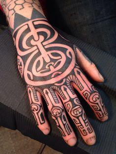 Dessus d'une main recouverte de tattoo maori